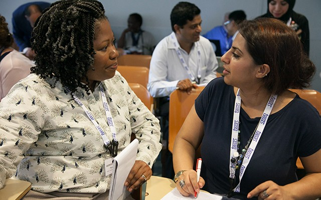 Participants Maria August Borges Cursino de Freitas Arruda, left, of the United Kingdom and Almas Taj Awan of Pakistan discuss the course with each other. (Photo: Demis Albertacci)